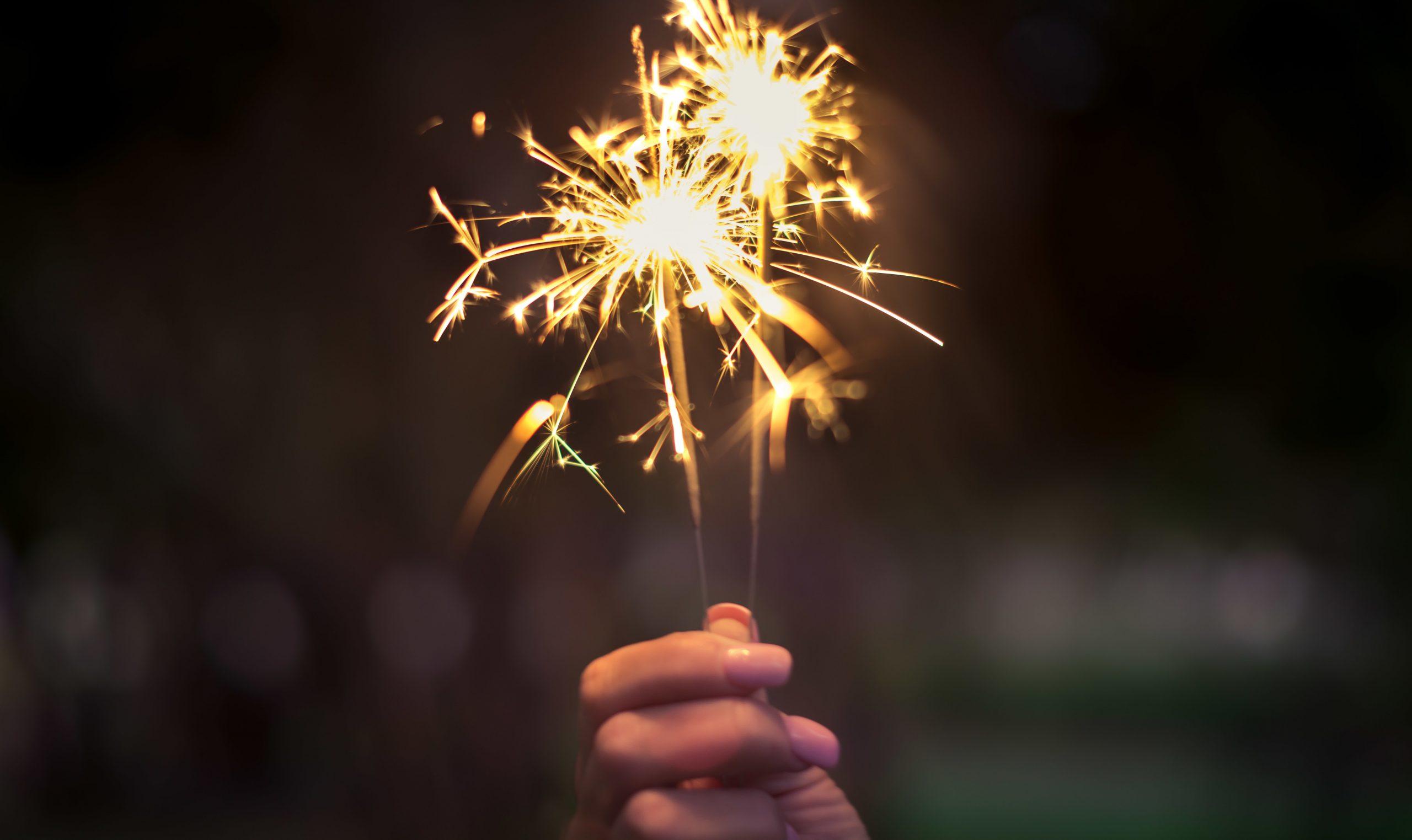 hand holding lit sparklers