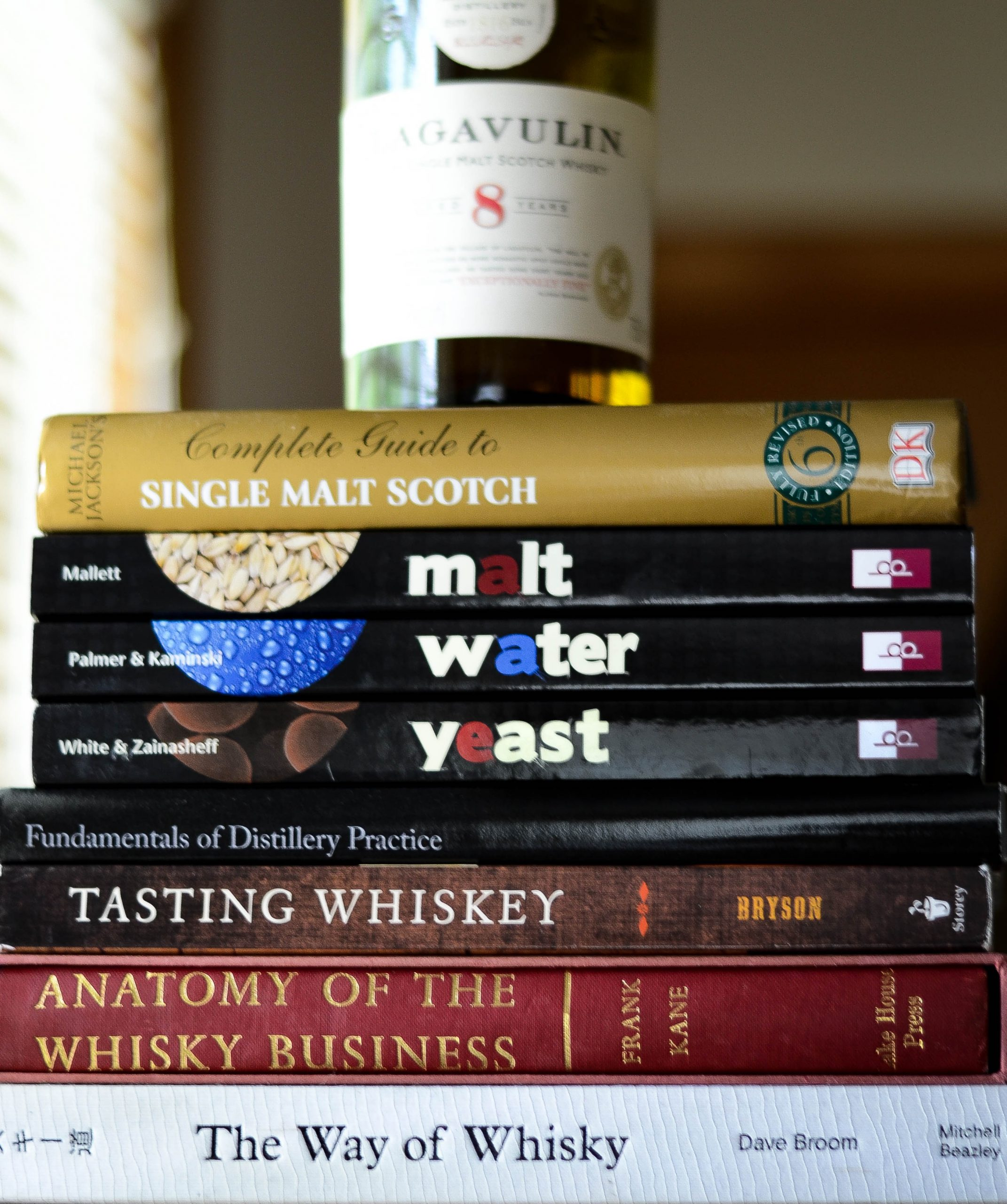 Stack of books about whiskey making with whiskey bottle on top