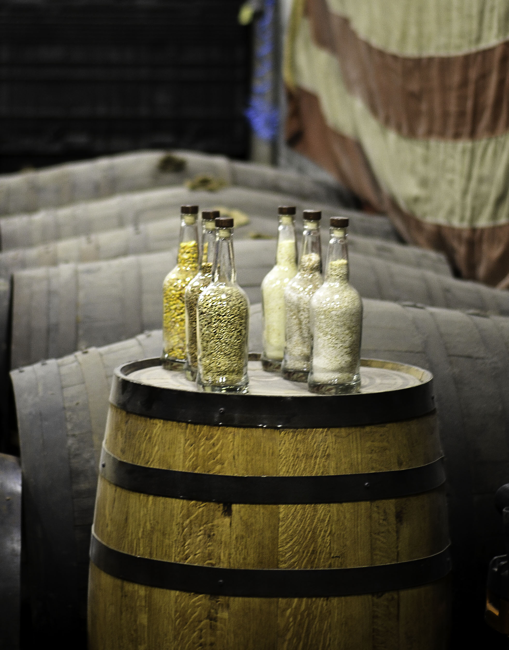 bottles of grain on top of a whiskey barrel